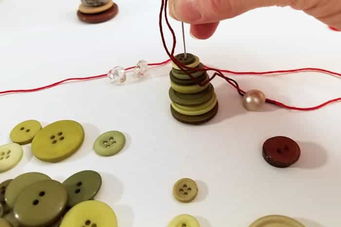 Needle threaded through stacked green buttons for button christmas ornaments.