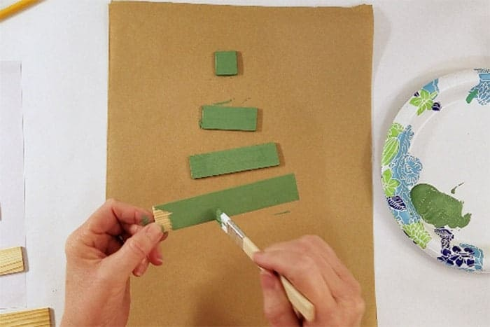 Paint sticks being painted green for christmas tree craft.