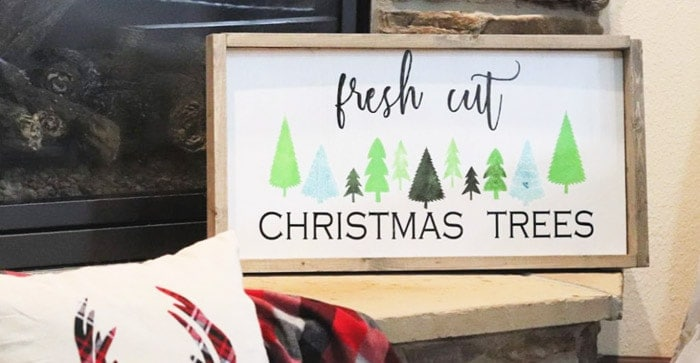 Fresh cut christmas tree sign with green and blue forest trees.
