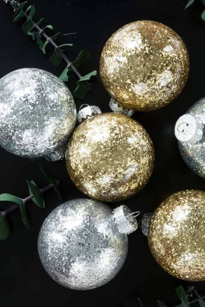 No mess glittery DIY Christmas Ornaments in gold and silver on black background.