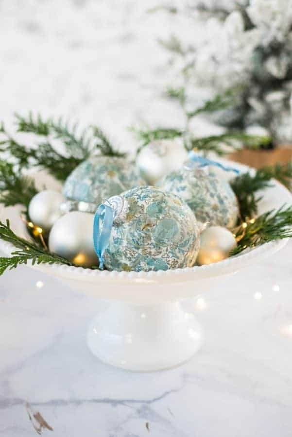 Decoupage DIY Christmas Ornaments in blue and white in a bowl with greenery.