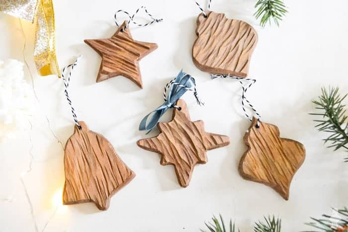 Wood-shaped DIY Christmas Ornaments on white shiplap.