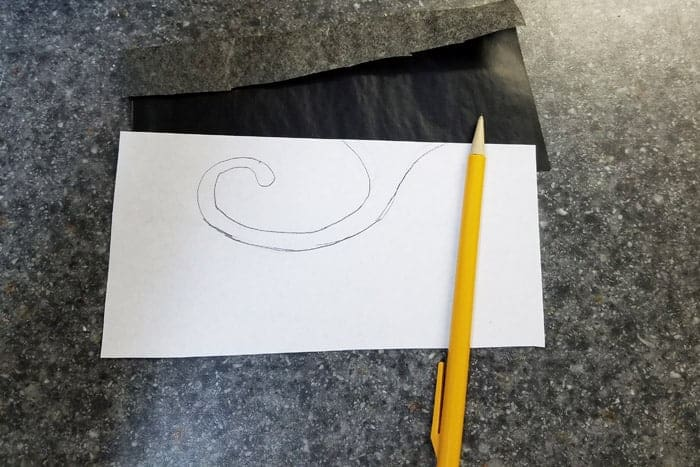 Swirl design on white paper and pencil