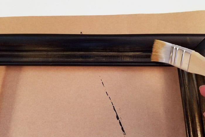 Dry brushing gold onto monogram door hanger frame.