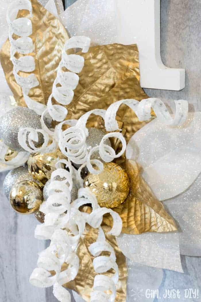 Glitter and ornaments on monogram door hanger.