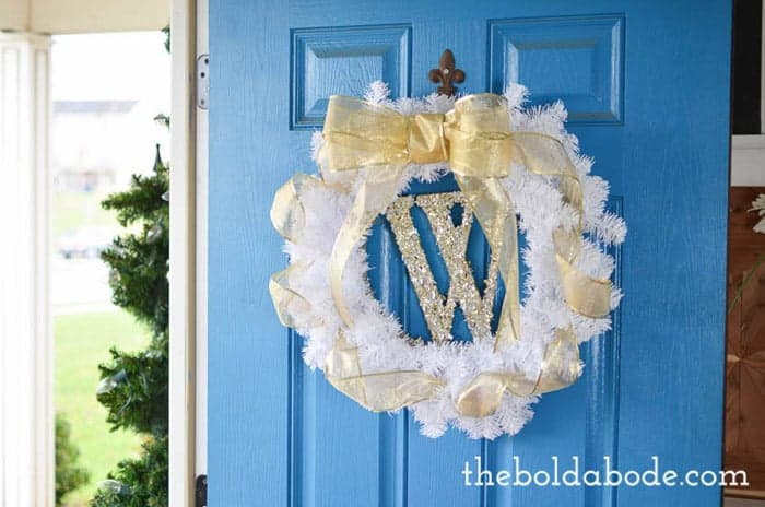 White and gold sparkly christmas wreath hung on blue door.