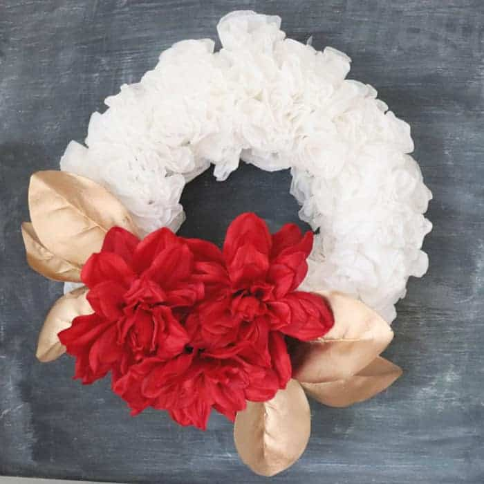sparkly christmas wreath with gold leaves and red flowers on a coffee filter wreath.
