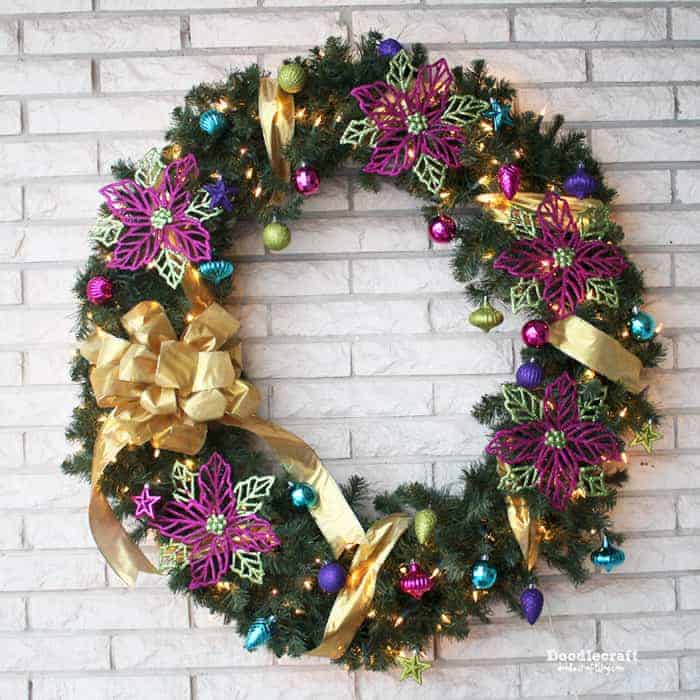 green and purple sparkly christmas wreaths on a brick wall.
