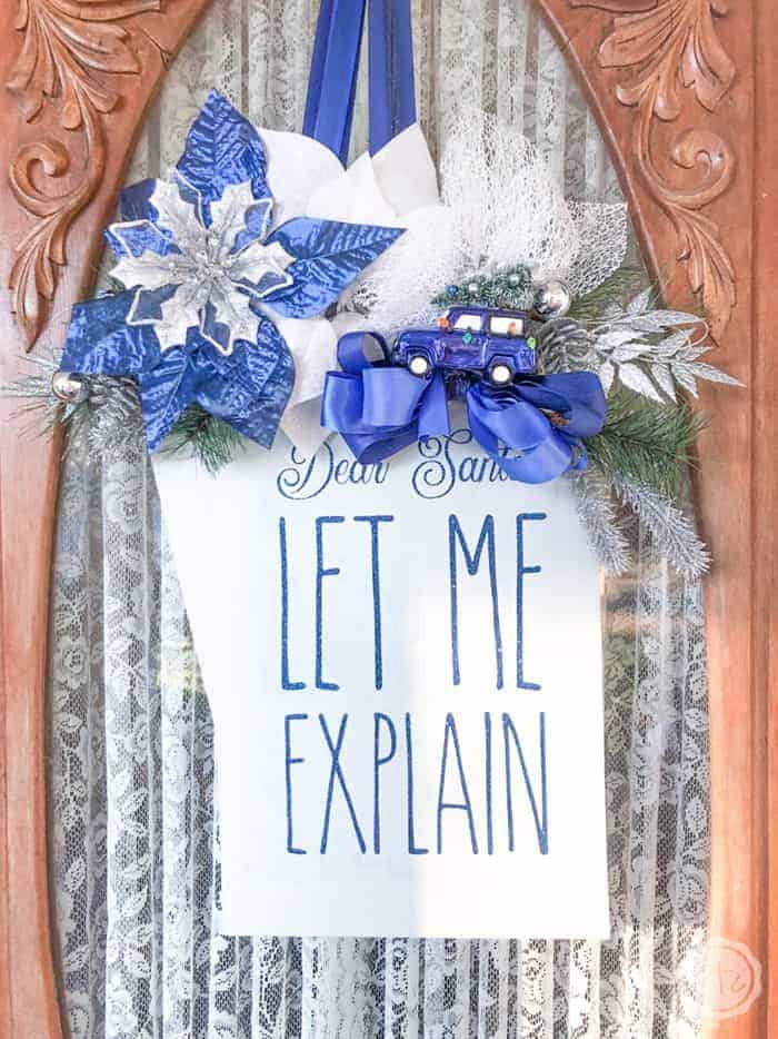 Sparkly christmas wreath that looks like a gift tag with blue flowers.