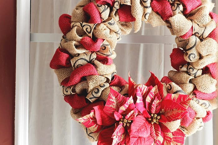 Burlap and red sparkly christmas wreath with red poinsettias.
