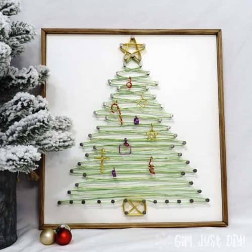 Completed String art Christmas tree on table near small faux flocked tree.