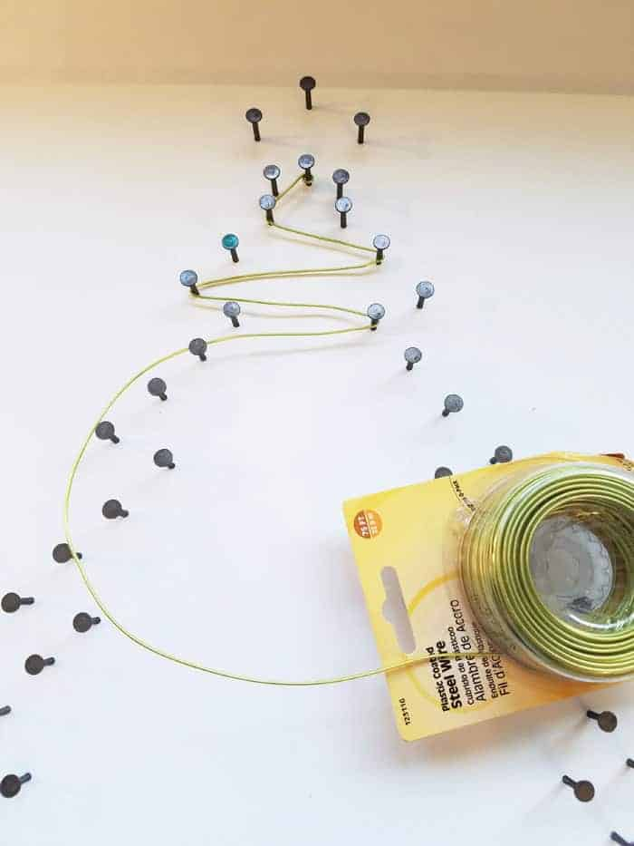 Wrapping green wire on every other nail on Christmas tree string art.
