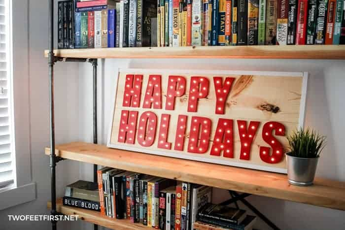 Lighted happy holiday sign red letters on pine board