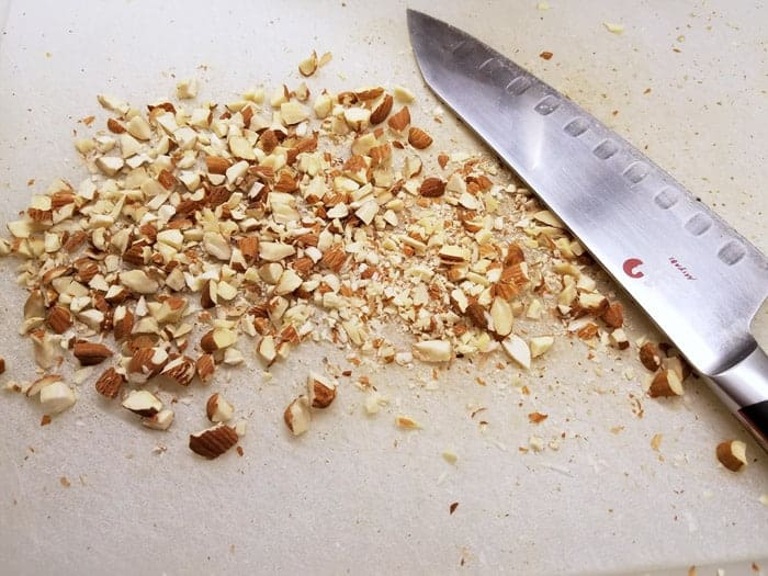 Chopped almonds on cutting board with chef's knife.