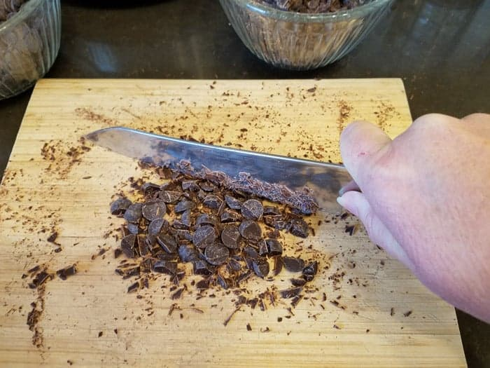 Chopping chocolate chips with chef's knife on cutting board.