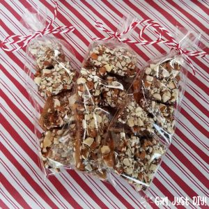 Homemade english toffee packaged in cellophane bags with red and white paper background