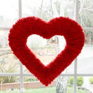 Square image of Double-sided fluffy valentine wreath hung in front window.