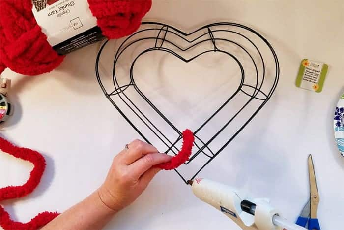 Gluing red fluffy yarn to heart-shaped wire wreath form.