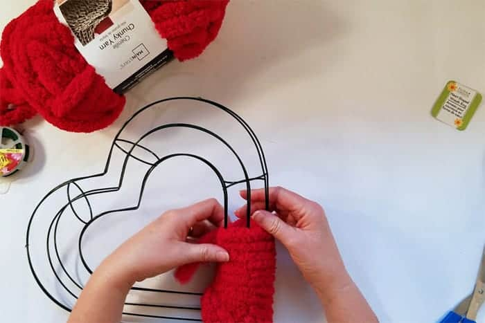 Wrapping red fluffy yarn around heart-shaped wire wreath form.