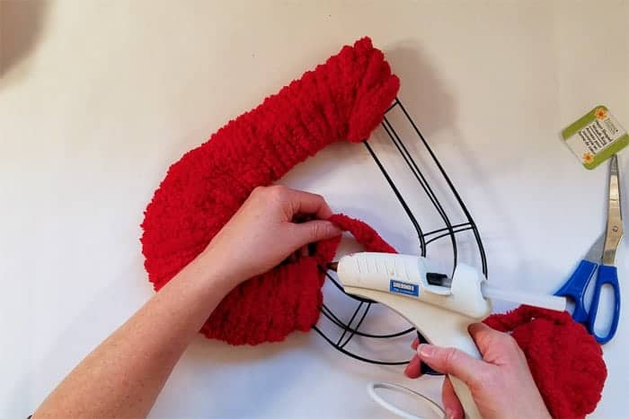 Gluing red fluffy yarn into point of wire heart valentine wreath.