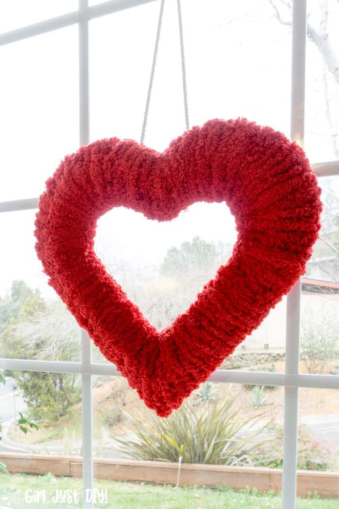 Closeup of Double-sided fluffy valentine wreath hung in window.