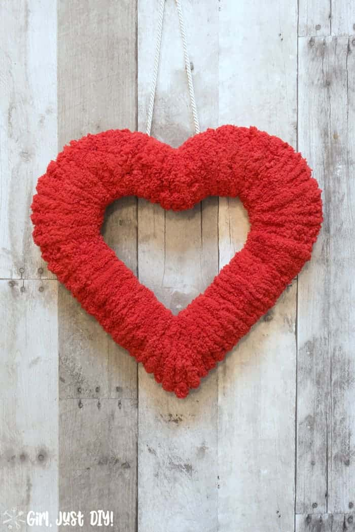 Fluffy valentine wreath hanging on wood wall.