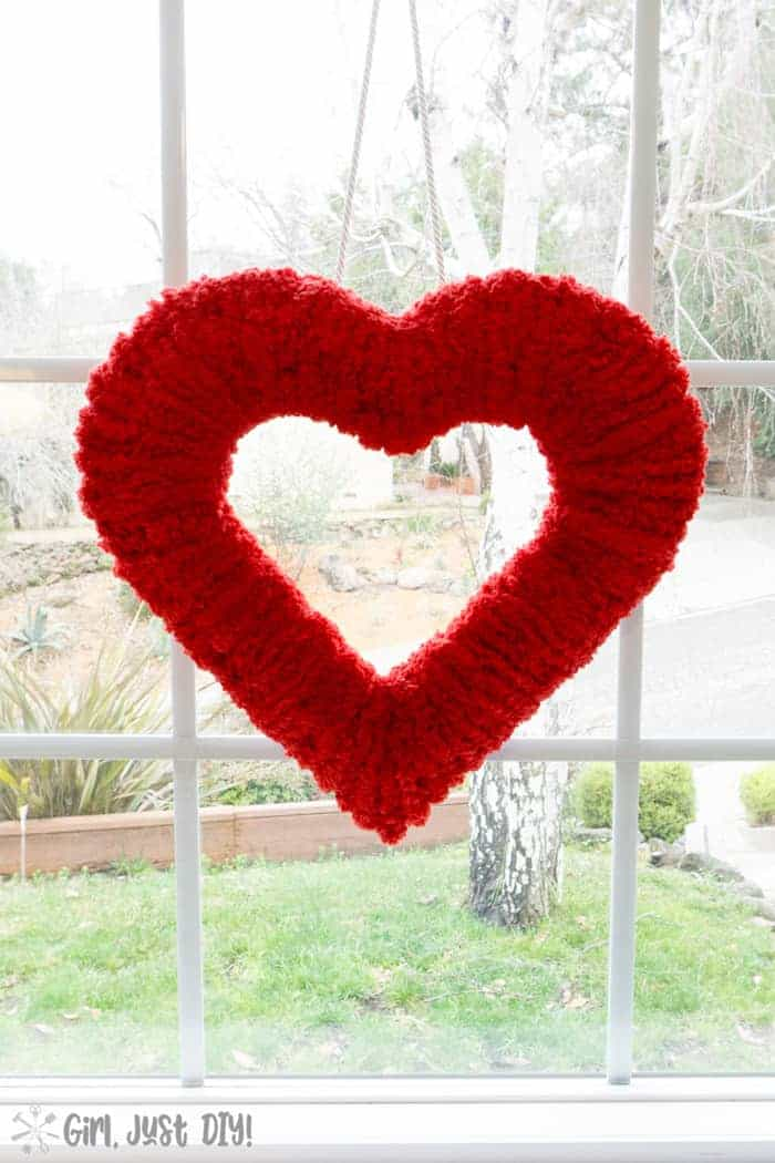 Double-sided fluffy valentine wreath hung in window.