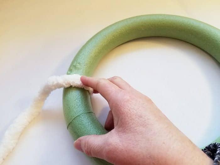 Pressing chenile yarn onto hot glue on green wreath form.