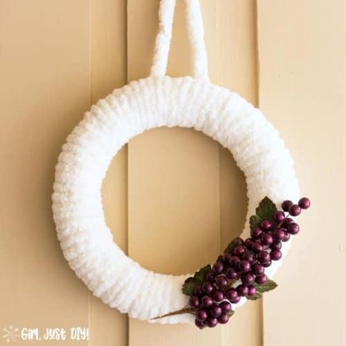 Completed white winter wreath with grape cluster hanging outside.