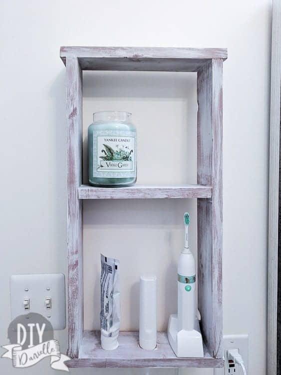 Wall shelve with electric toothbrush and supplies.