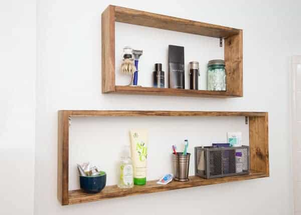 Shallow square wall shelves in bathroom with grooming supplies.