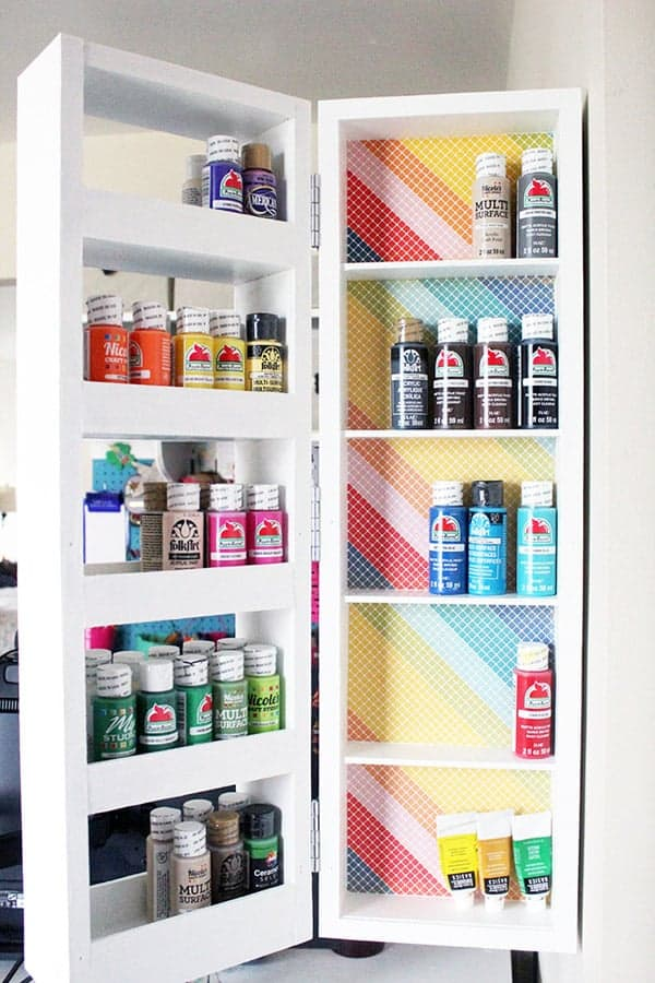 Fold out shelves filled with colorful craft paint.