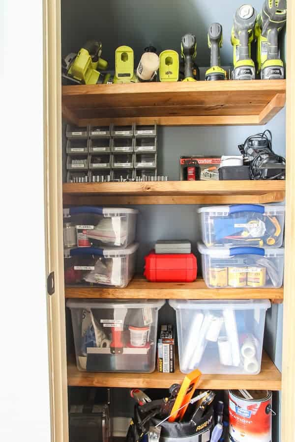 Garage tools and bins on wood shelves in closet.