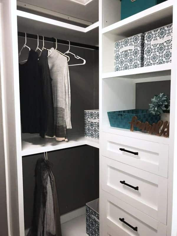 White closet Organizing system with clothes hanging and colored boxes on shelves.