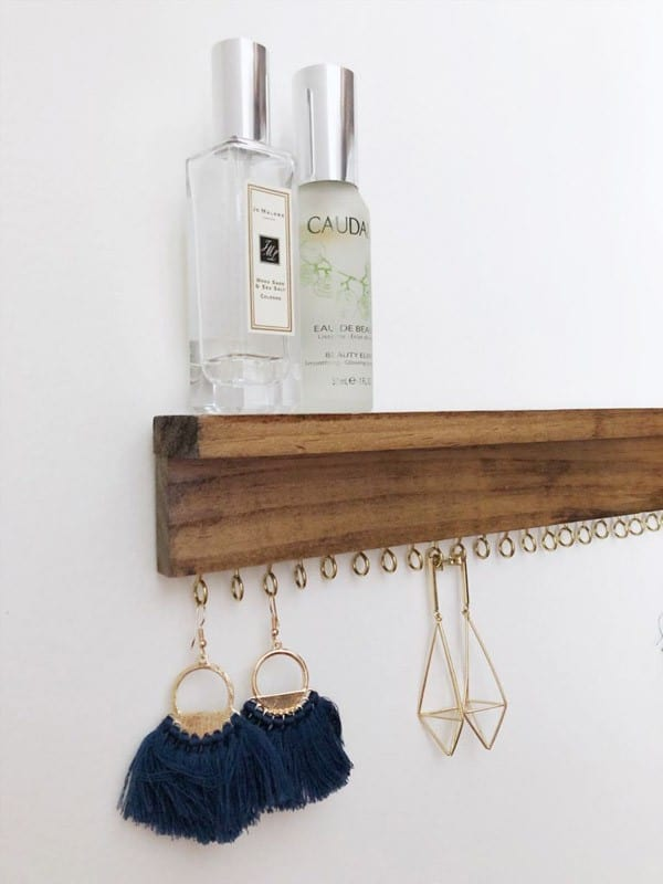 Narrow shelve with perfume on top and earrings hung on hooks below.