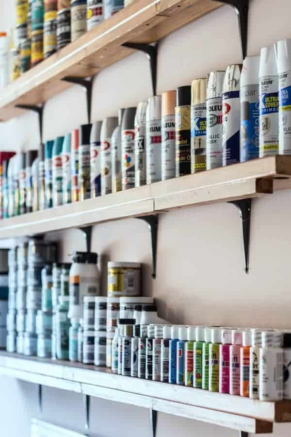 Narrow shelves lined with colorful paint cans.