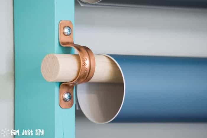 Closeup of tube strap and a roll of vinyl hanging on the dowel.