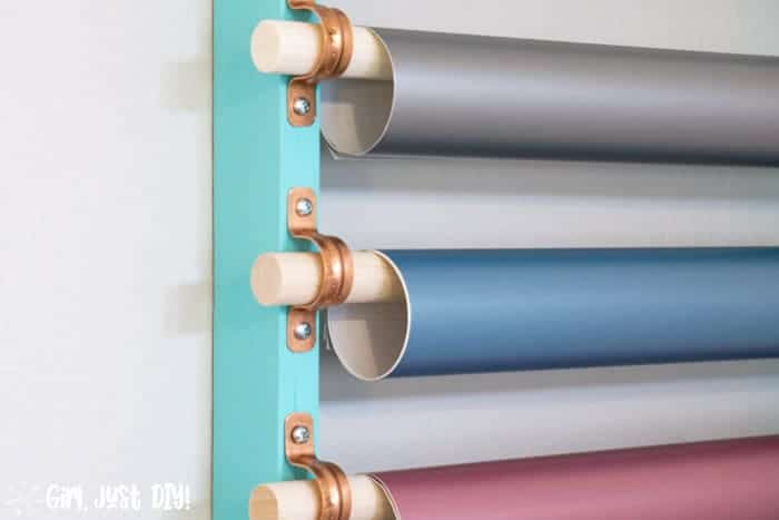 Three rolls of vinyl hanging on dowels.
