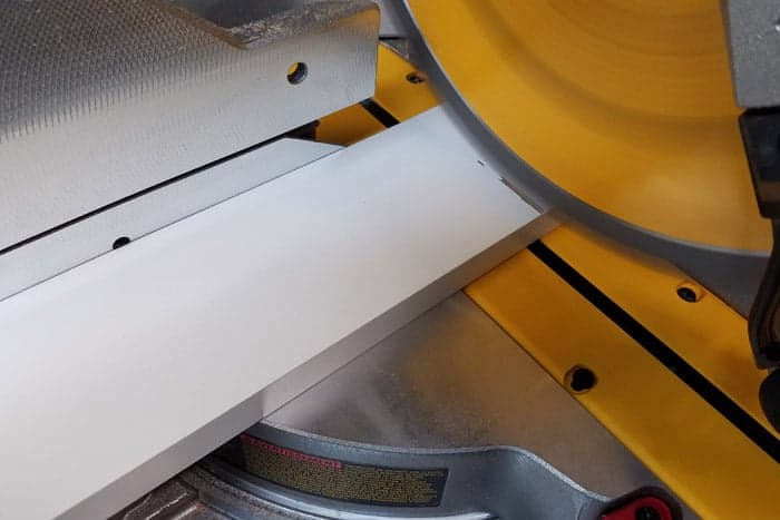 Miter saw blade cutting into white board for vinyl storage rack