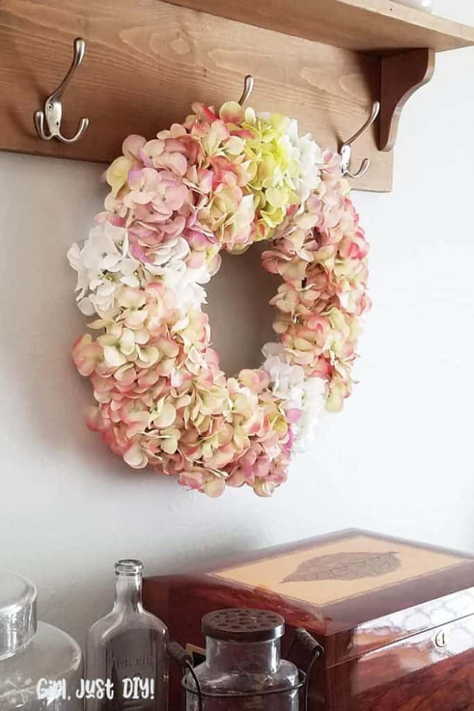 Faux Hydrangea wreath hanging on hook in dining room.