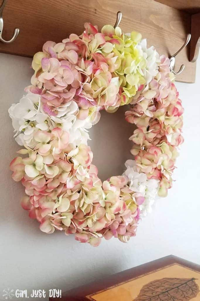 Faux Hydrangea wreath hanging on hook over buffet.