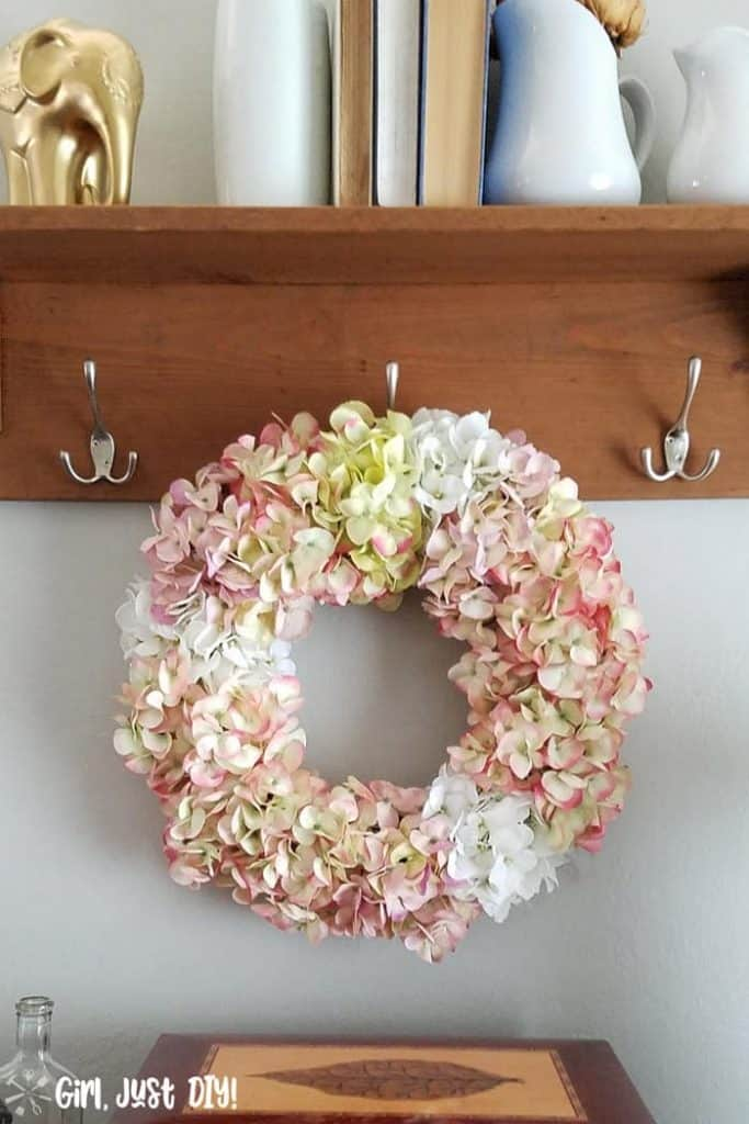 Faux Hydrangea wreath hanging on coat rack hook.