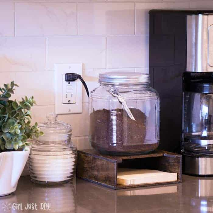 Wood coffee filter holder on counter top next to coffee maker.
