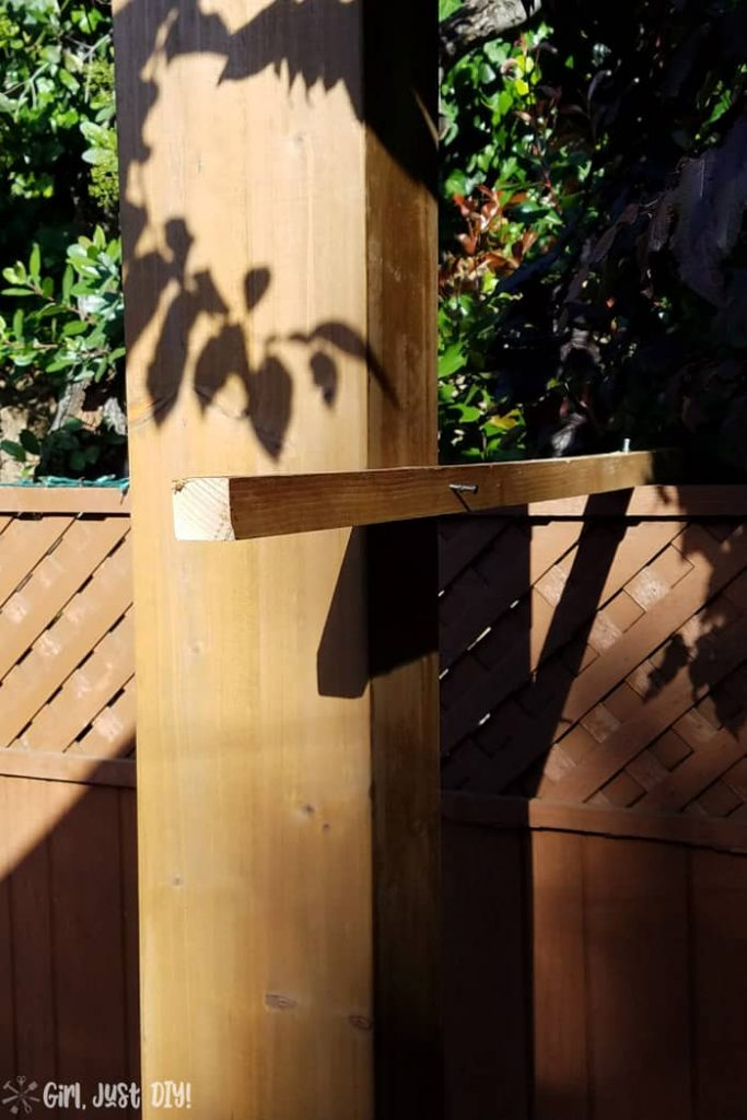 wood 2x2 attached to fence and post of diy patio gazebo.