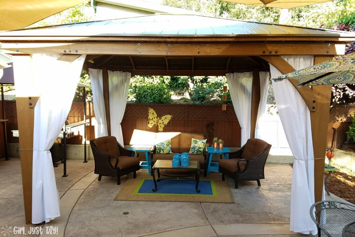 Patio furniture and curtains hung on diy patio gazebo.