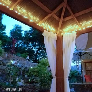 Yard view of diy patio gazebo with lights on.