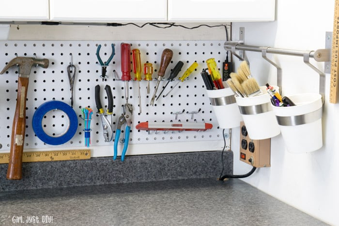Screwdrivers and pliers hanging form pegboard installation.