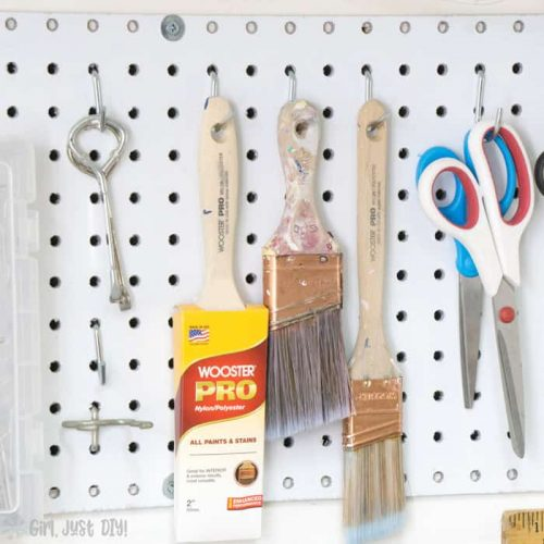 Paint brushes and scissors hanging on pegboard.