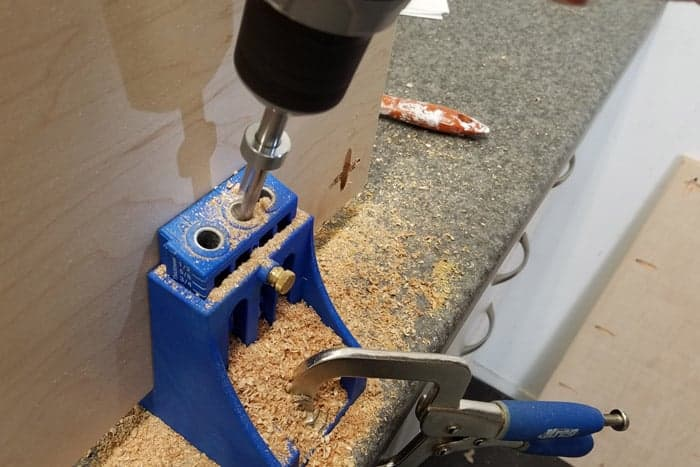 Closeup of drilling pocket holes into plywood.