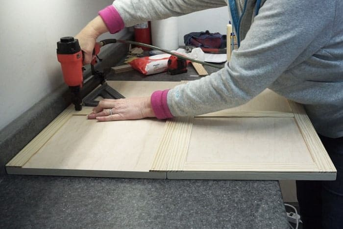 Attaching trim to doors with brad nailer.